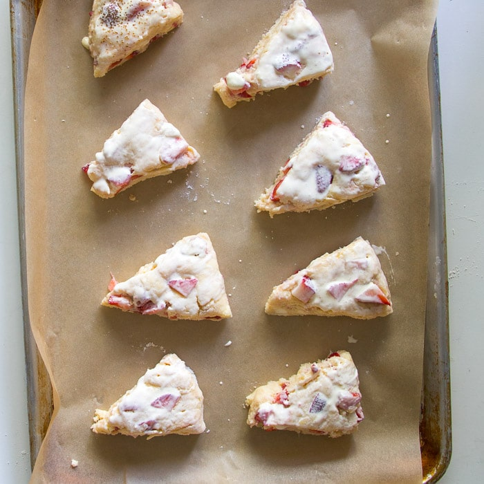Unbaked strawberries and cream scones on a sheet pan brushed with cream ready to be baked