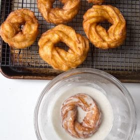 Crullers being dipped in powdered sugar glaze