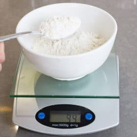 A scale with flour in a bowl showing the weight