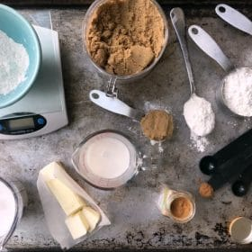 Various ingredients, dry and wet measuring cups and spoons and a scale