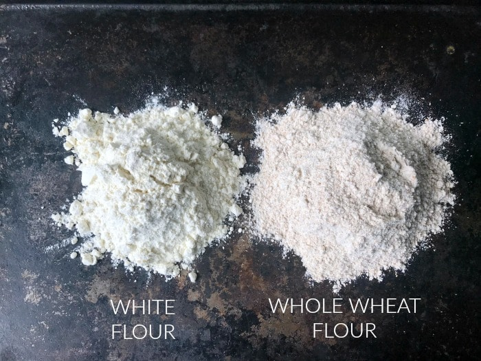 Spooned out onto a surface: white flour on the left, whole wheat flour on the right