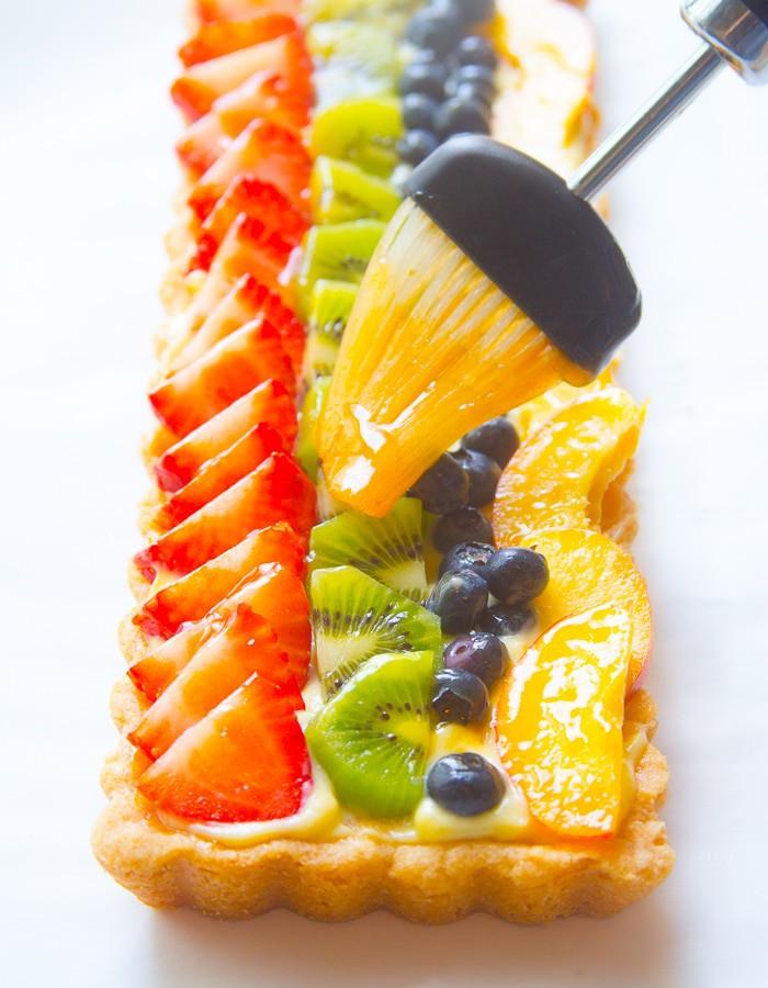 Fruit tart being glazed with fruit glaze