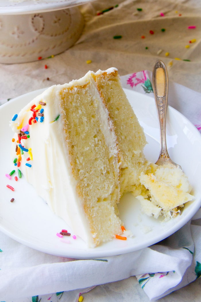 A slice of white cake with vanilla frosting