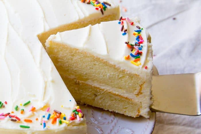 White layered cake topped with vanilla frosting and colorful sprinkles