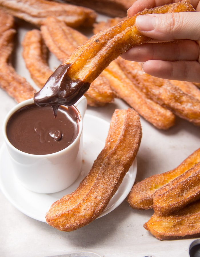 Hommade churros being dipped in chocolate dipping sauce