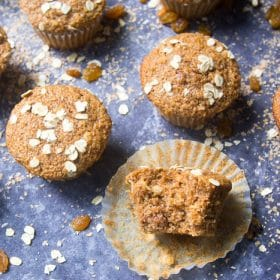 Bran muffins lined up with one muffin having a bite taken out of it to expose the texture inside