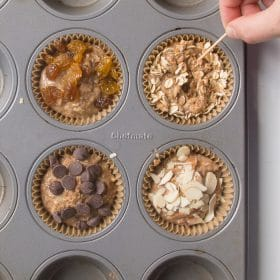 Batter poured into muffin cups topped with various toppings like raisins and shredded coconut