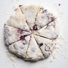 Blueberry scone dough being cut into triangles