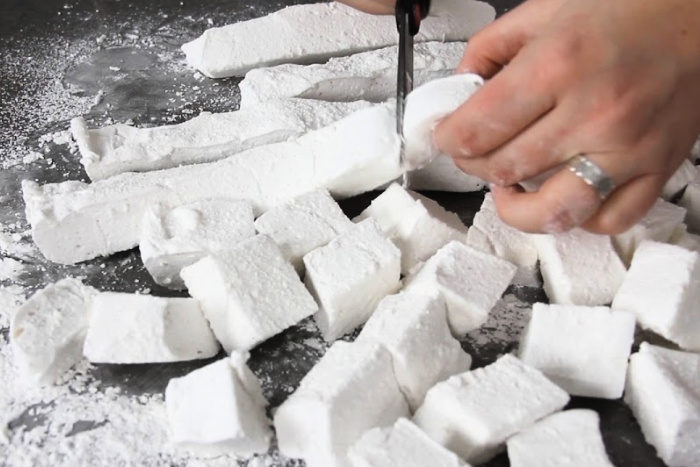 Cutting marshmallows into cubes with scissors