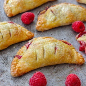 Golden turnovers in a half moon shape filled with raspberry jam on a tray