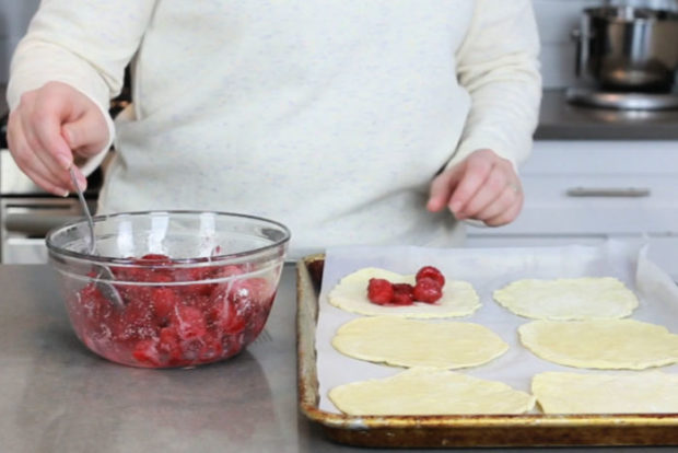 Filling dough circles with raspberry mixture on parchment lined tray