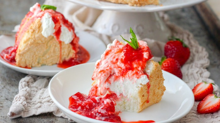 2 slices of angel food cake topped with fresh strawberry sauce, whipped cream and a mint sprig