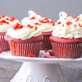 Red velvet cupcakes on a plate beautifully decorated with cream cheese frosting