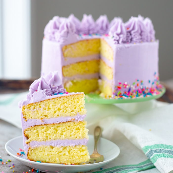 A slice of layered chiffon cake with frosting