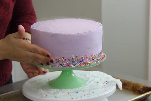 Pressing sprinkles onto the bottom half of the cake
