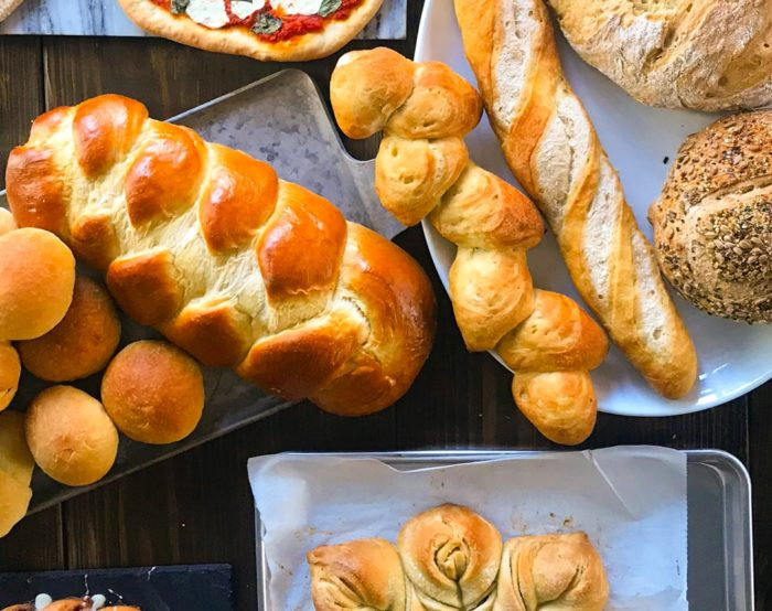 A display of various types of breads: challah, epi bread, baguettes, star bread, etc