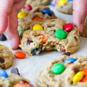 Monster Cookies filled with chocolate chips, nuts and M&Ms on a sheet tray with a bite taken out of one