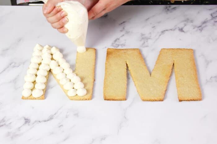 Piping dollops of buttercream on the cream tart cake