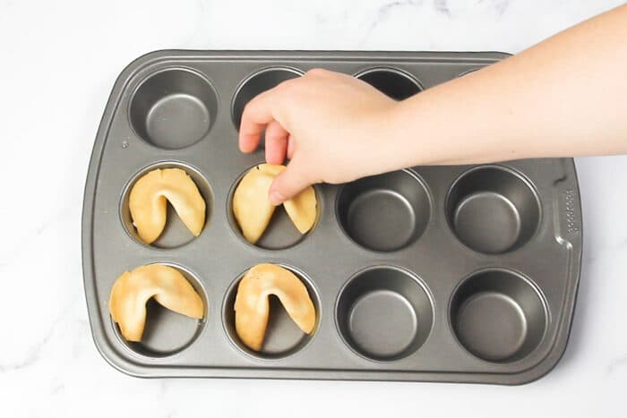 Placing fortune cookies into a muffin tin after shaping to help them hold their shape while cooling