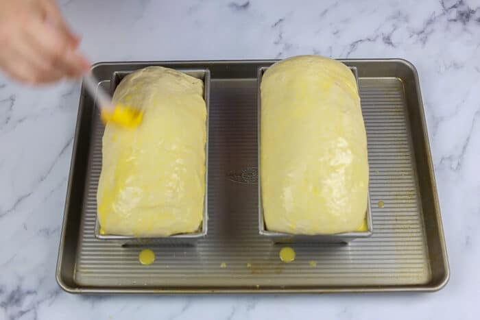 Brushing egg wash on the sandwich loaves