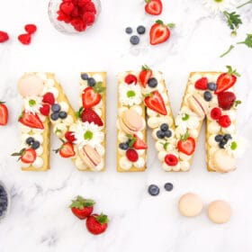 "A beautiful cream tart in the shapes of an ""N"" and ""M"" decorated with flowers, fresh fruits and macarons"