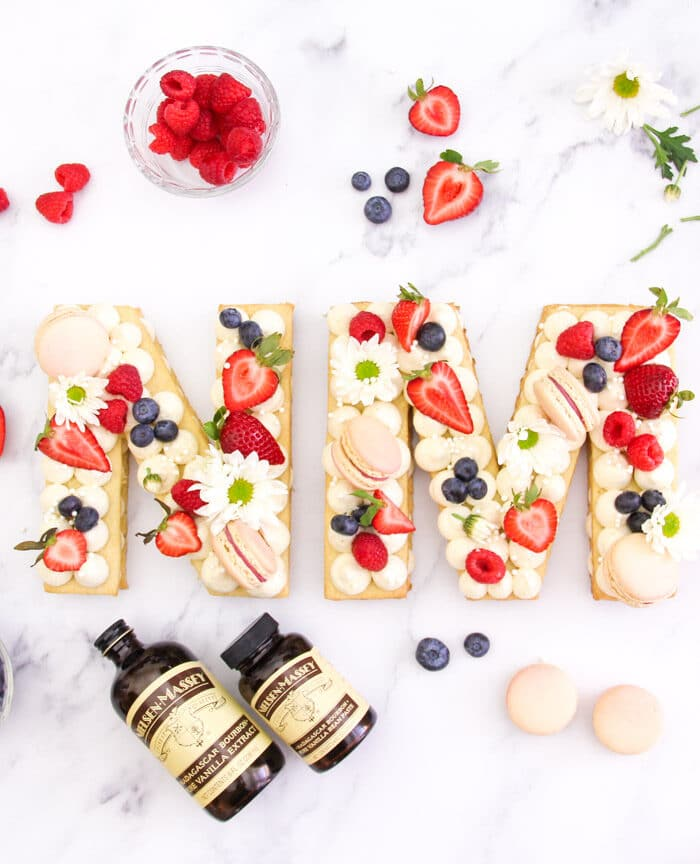 """A beautiful cream tart in the shapes of an """"N"""" and """"M"""" decorated with flowers, fresh fruits and macarons"""