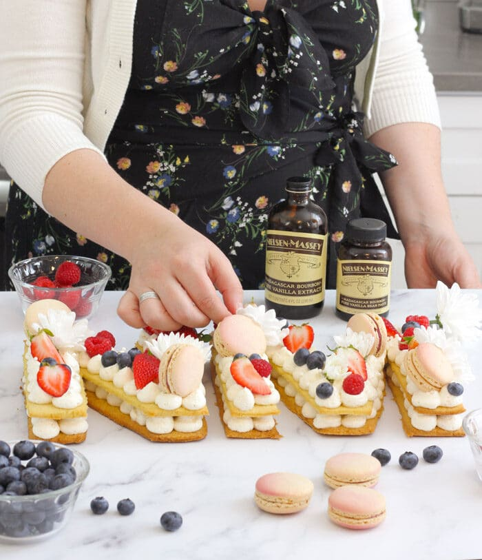 Decorating the cream tart with fresh flowers, macarons and flowers