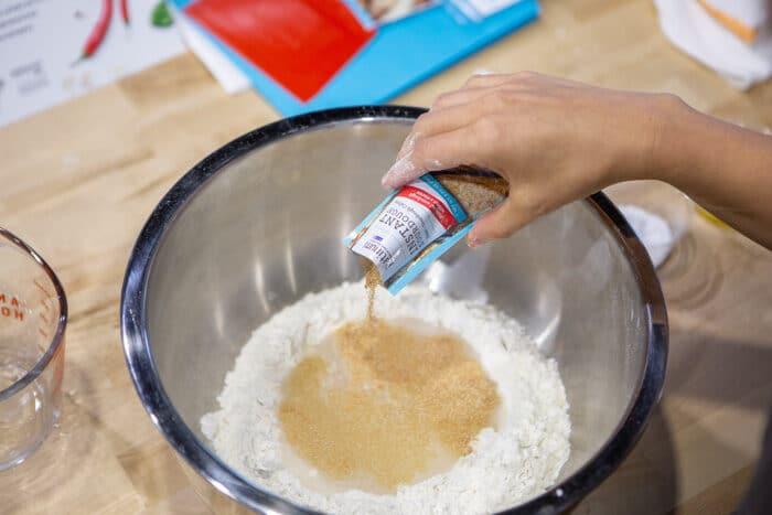 Adding platinum instant sourdough into a bowl to make pizza dough