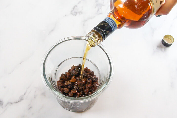 Pouring bourbon over raisins to soak them