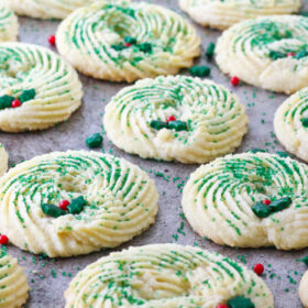 Butter Spritz cookies decorated to look like a wreath all lined up for a beauty shot