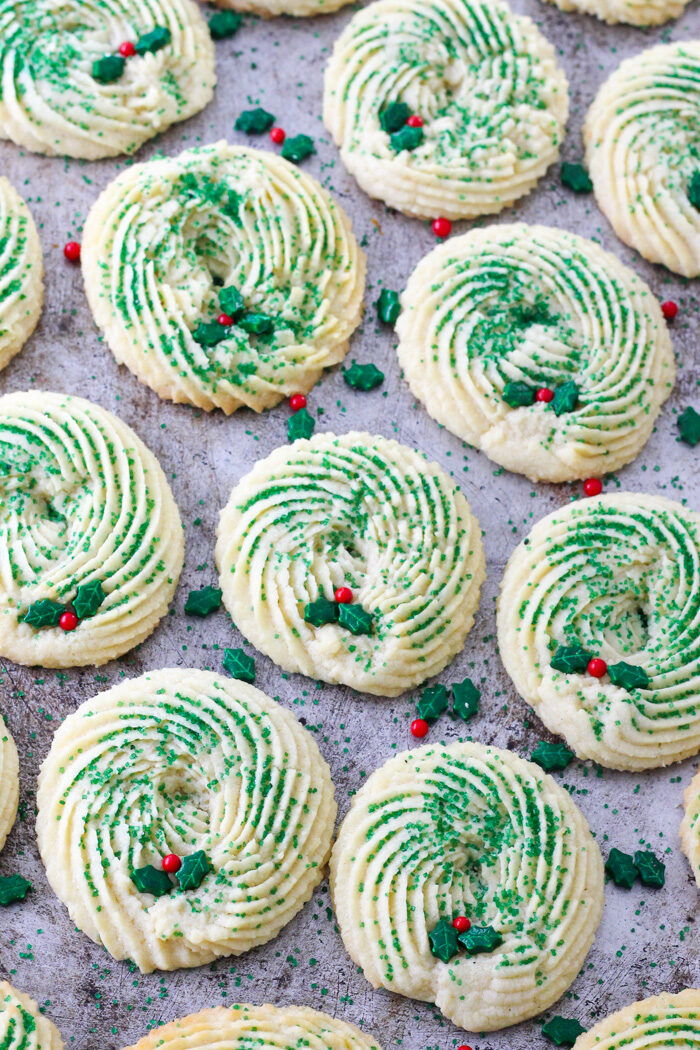 Tray of butter spritz cookies that are shaped like christmas wreaths and decorated with holly berry sprinkles