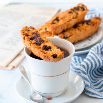 Cranberry Orange biscotti resting on a cup of coffee