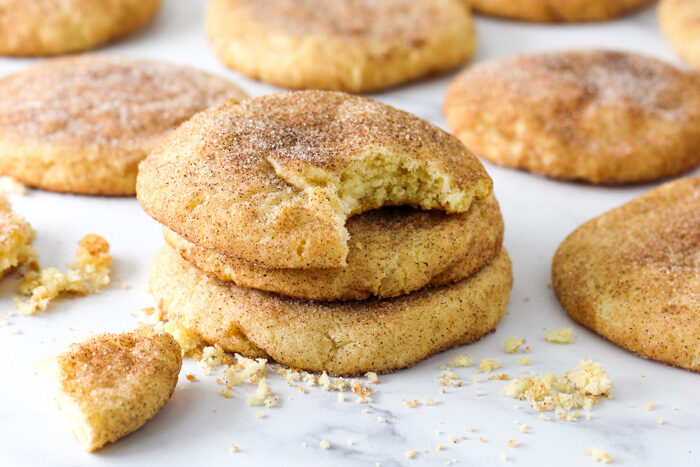 Snickerdoodles on a sheetpan, one with a bite taken out