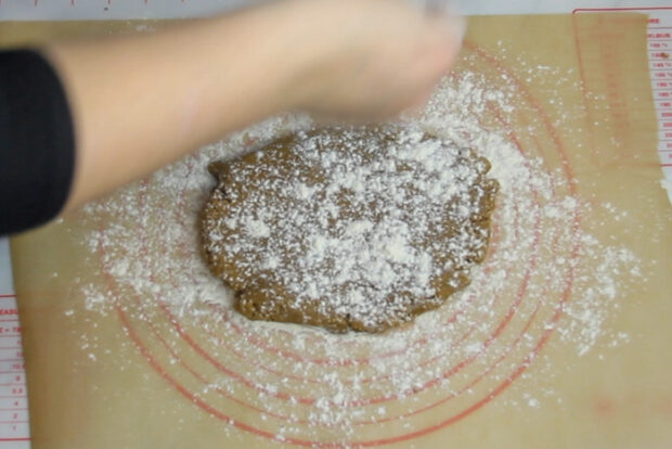 Dough out on a piece of parchment paper and sprinkling flour on top of dough
