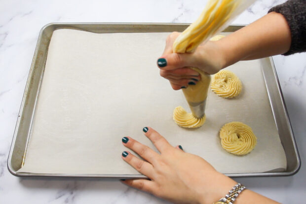 Piping spritz cookie dough onto parchment lined baking sheets