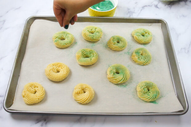Sprinkling green sanding sugar onto the shaped cookie dough