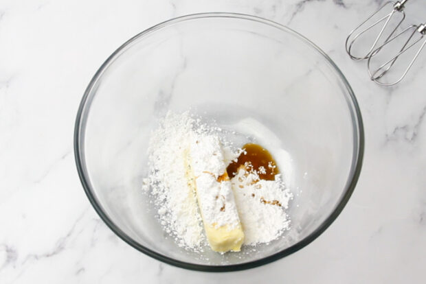 Large mixing bowl with butter, powdered sugar, and vanilla in it