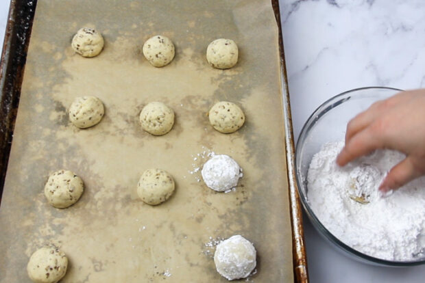 Tossing warm snowball cookies into powdered sugar