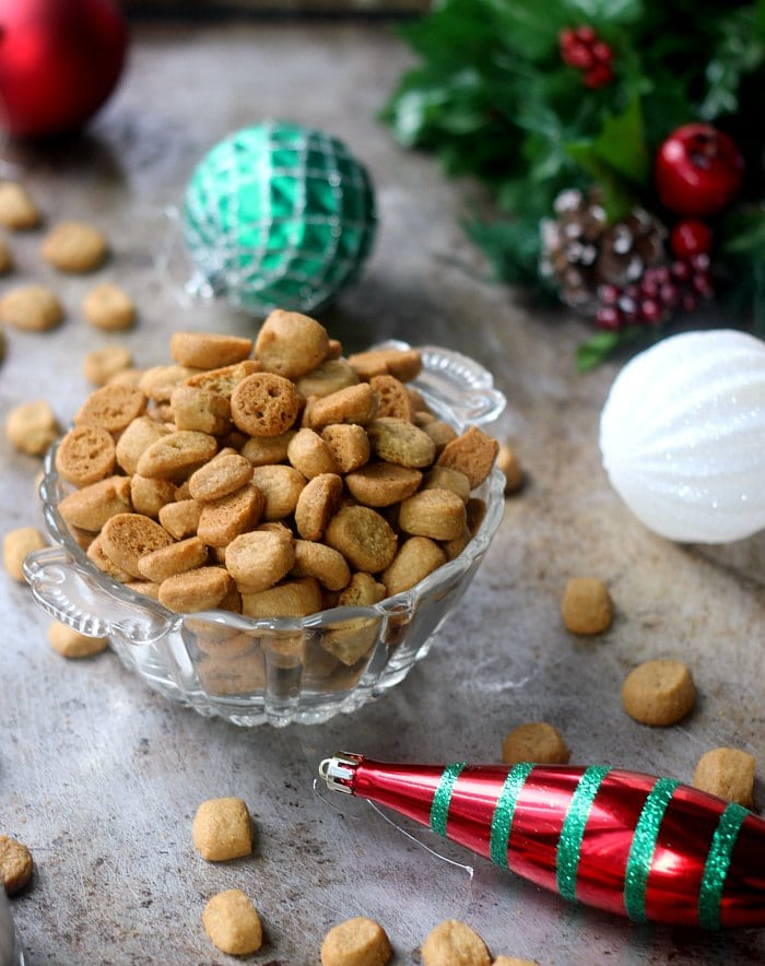 Peppernut cookies in a candy bowl surrounded by holiday ornaments