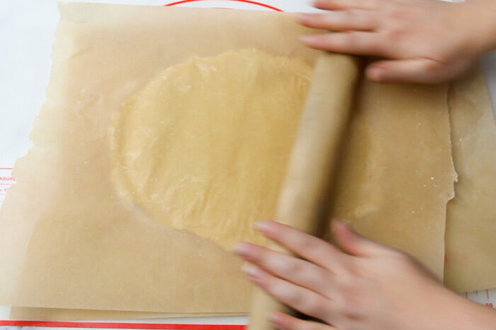 Rolling out sugar cookie dough in between two pieces of parchment paper