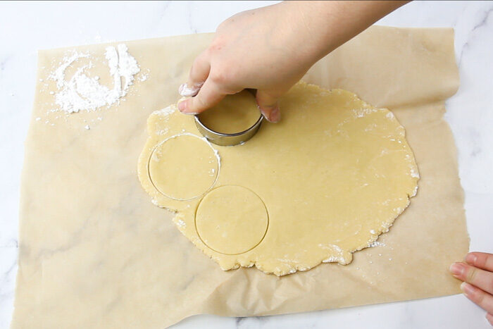 Cooke dough rolled out and a being cut into circles with a round cookie cutter