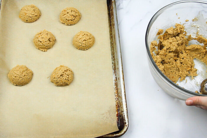 Scooping sweet potato dough onto a parchment lined baking sheet