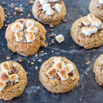 Sweet potato cookies topped with pecans and toasted marshmallows lined up on a baking sheet