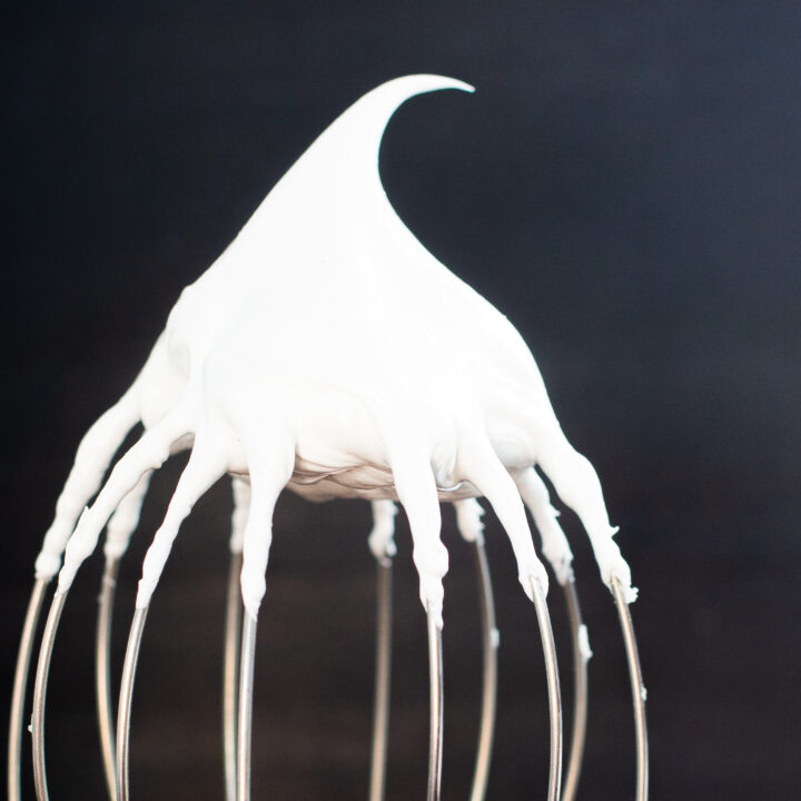 Stiff meringue on a whisk holding its peak