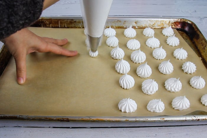 Sheet pan lined with parchment and meringue cookies are being piped onto it
