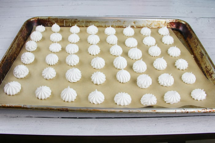 Sheet pan filled with meringue cookies after being baked