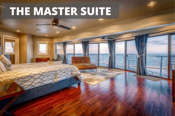 Large bedroom with a large bed and windows called the Master Suite