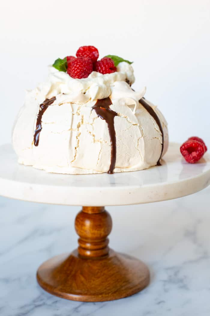 Pavlova topped with chocolate ganache, cream and fresh raspberries on a cake stand