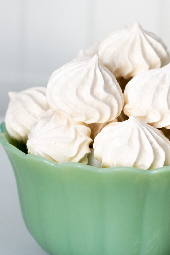 Meringue kisses piled up in a green bowl on a white background