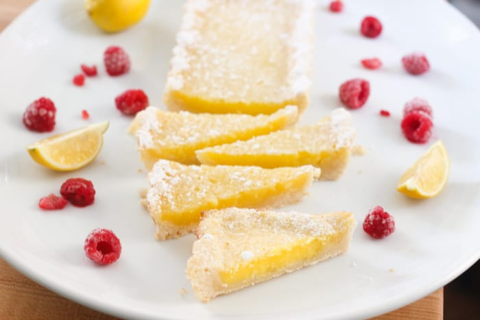 Lemon tart on a white platter. There are 4 slices cut and the top is dusted with powdered sugar and there are raspberries on the platter for decoration